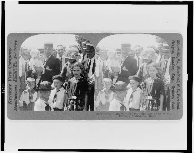 Pres. Harding holds the baby and talks to the farmers, Hutchinson, Kansas