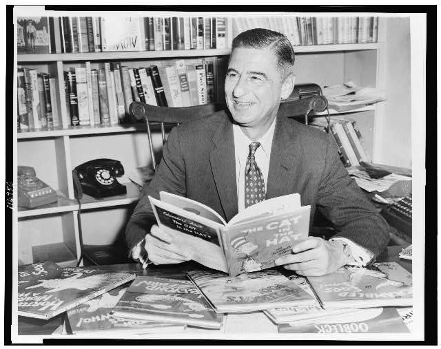[Ted Geisel (Dr. Seuss) half-length portrait, seated at desk covered with his books]