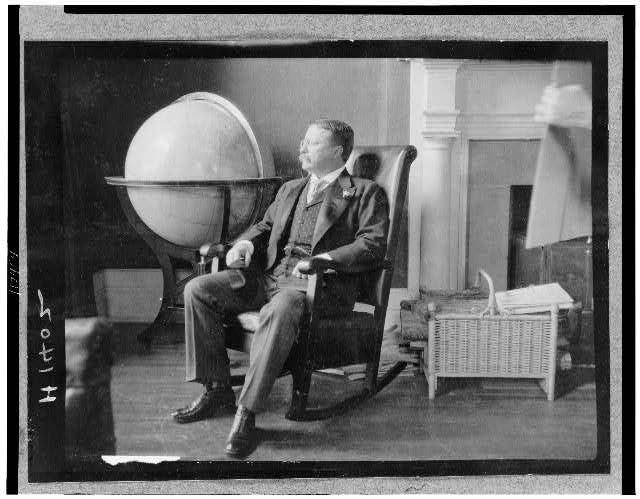 [Theodore Roosevelt, full-length portrait, seated in rocking chair, facing left, by large globe]