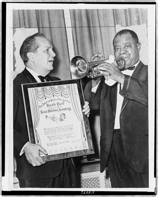 [Louis Armstrong plays trumpet while Joey Adams, president of the American Guild of Variety Artists Youth Fund, presents him with an award at Carnegie Hall]