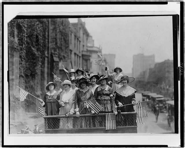 [Group of women standing on top of vehicle waving flags, New York City]