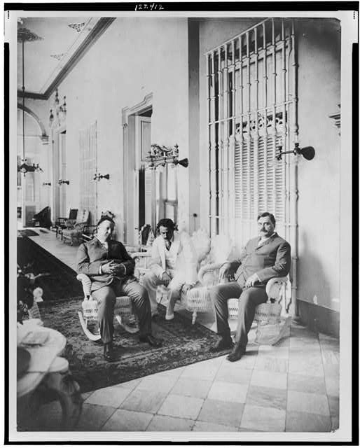 [William Howard Taft, full-length portrait, seated on rocking chair, facing right, with two other men]