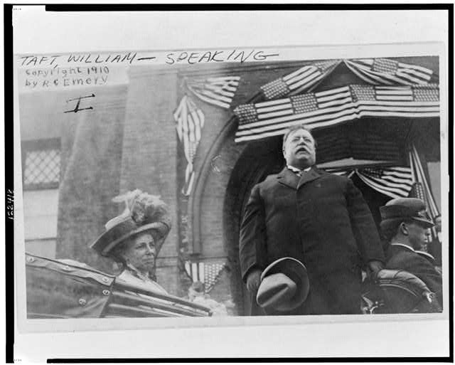 [William Howard Taft, half-length portrait, standing in back of open-air car, facing front, speaking, with his wife]