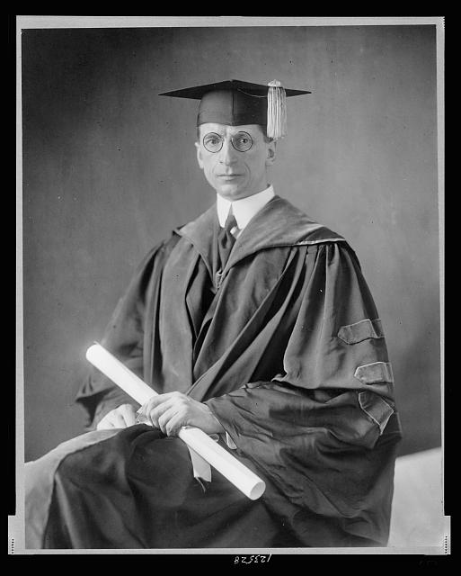[Eamonn De Valera, three-quarter length portrait, seated, facing front, wearing cap and gown]