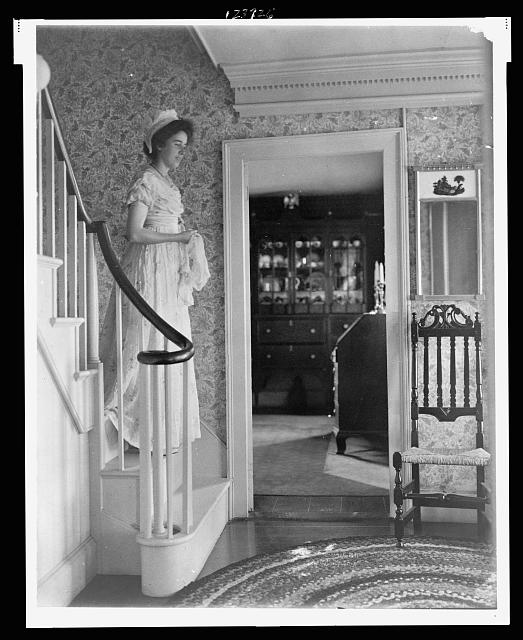 [Young woman in colonial dress on steps in Colonial- American home]