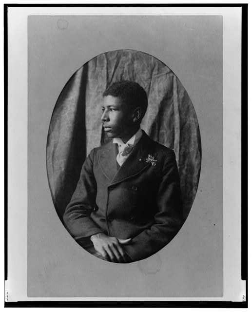 [Young African American man, half-length portrait, seated, facing left]