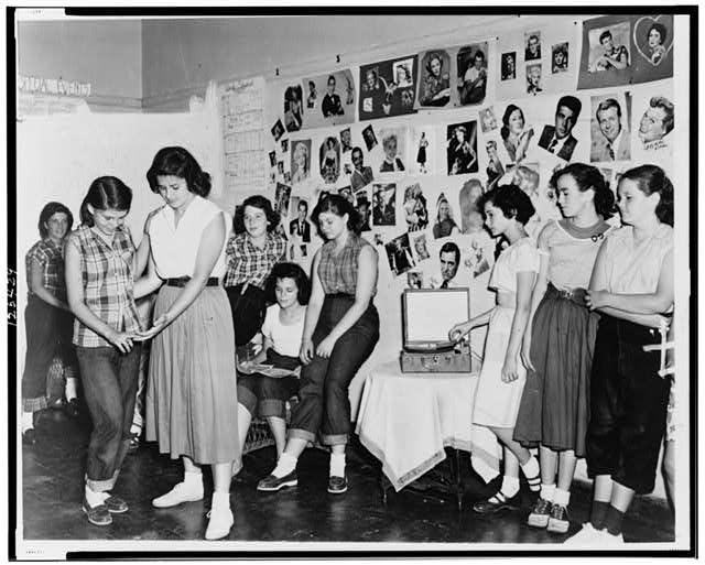 Showing recreation instructor Miss Eleanor Kenny teaching her teenage group how to dance--The pictures on the wall are the girls favorite screen stars