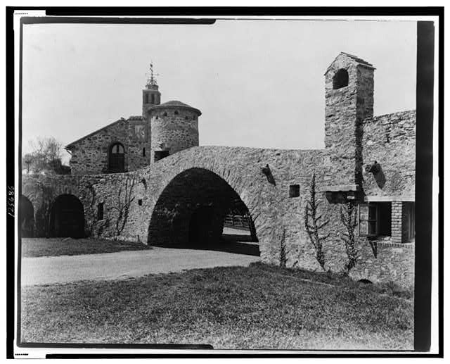 "[""Surprise Valley Farm,"" Arthur Curtiss James property, Beacon Hill Road, Newport, Rhode Island. Archway with stone buildings]"