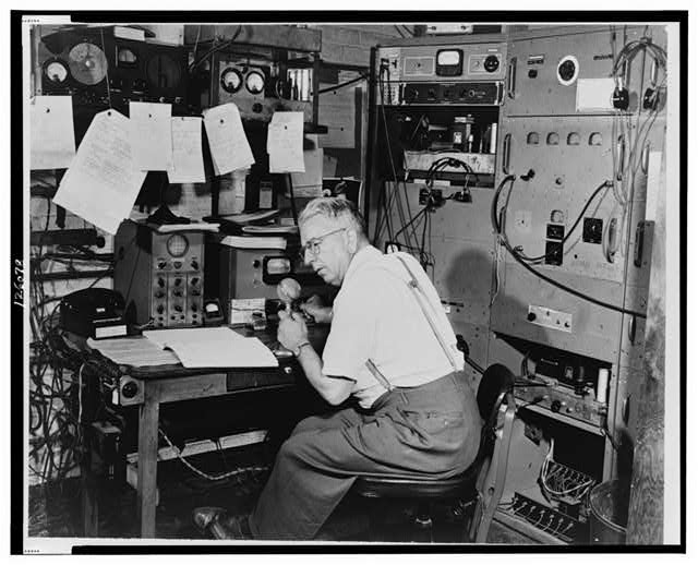 Ted Gempp, operator of the radio station at Alpine, N.J., shown at microphone in the control room of the station