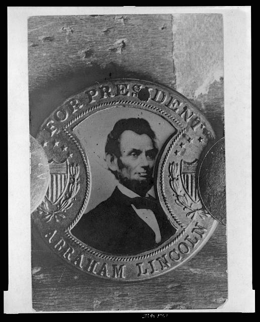"[Photograph of a campaign button with portrait of Abraham Lincoln and inscription ""For President Abraham Lincoln""]"