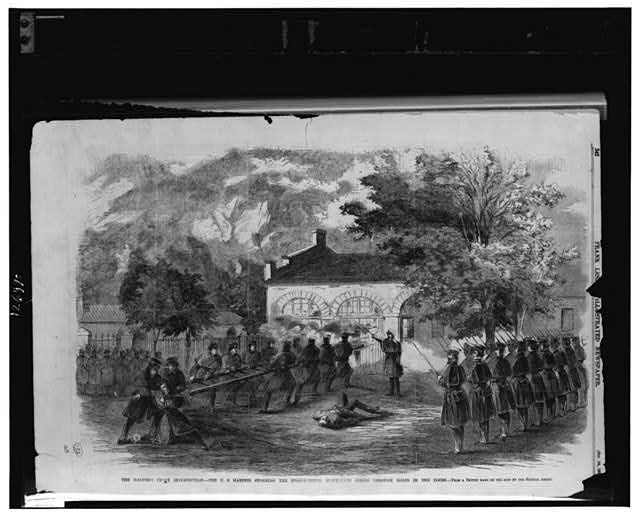 The Harper's Ferry insurrection--The U.S. Marines storming the engine house--Insurgents firing through holes in the doors / from a sketch made on the spot by our special artist.