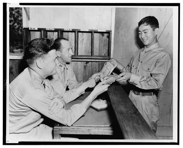 A reminder of the nation's tremendous war loan drive is Private Jack Y. Oato of Company G, 442 Infantry, who paid cash on the line from $2,500 worth of war bonds--Above Private Oato hands over a fistfull of bills for bonds to Captain F. W. Vowell, his company commander, and Second Lieutenant Arthur MacColl