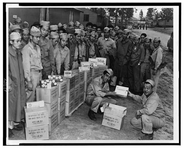 Private Sam Oka hands over to Private Henry Oshiro his share of the generous gifts of candies and cigarettes sent to members of the Japanese-American Combat Team by a Hawaiian pineapple company