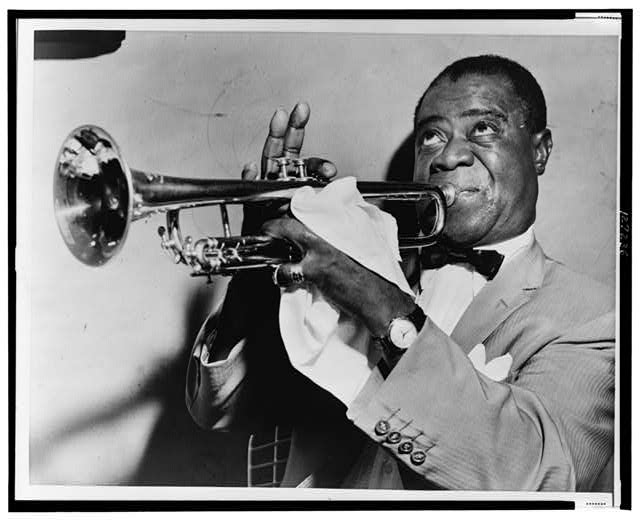 [Louis Armstrong, head-and-shoulders portrait, facing left, playing trumpet]