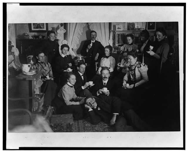 [Group portrait of friends at social gathering, seated and standing with tea cups, in domestic setting]