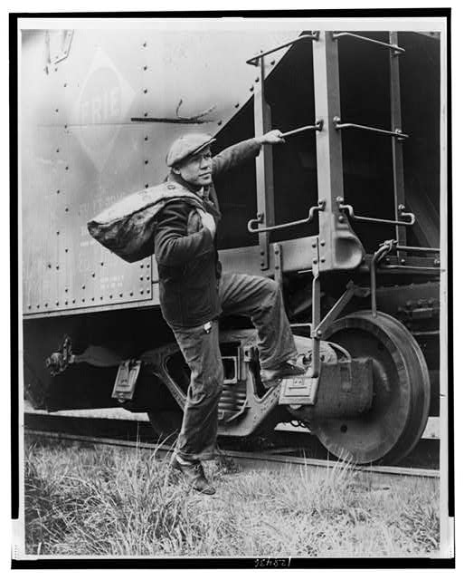 [Lou Ambers with a large bag over his shoulder, mounting the ladder of a train car]