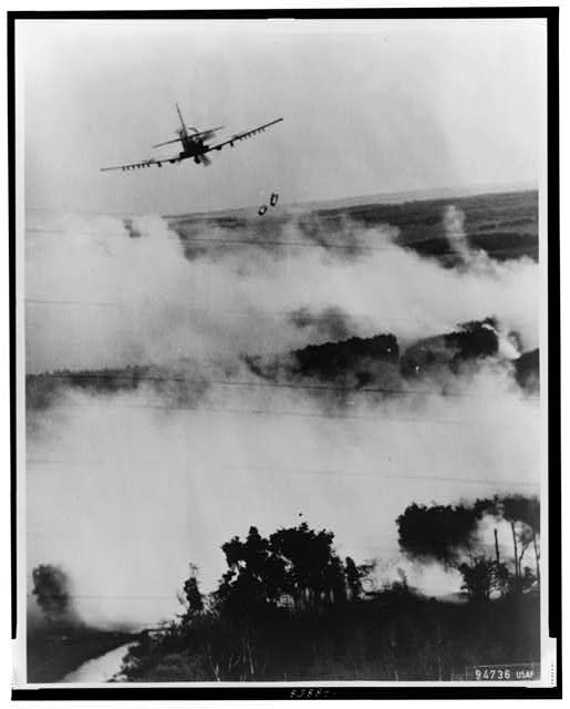 Two bombs tumble from a Vietnamese Air Force A-1E Skyraider over a burning [Viet] Cong hideout near Cantho, South Viet Nam