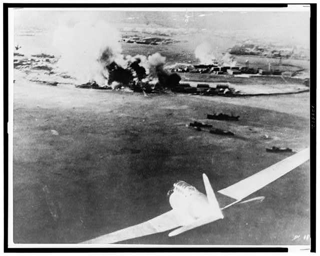 [Aerial photograph, taken by a Japanese pilot, of the destruction of Pearl Harbor, Japanese bomber in lower right foreground]