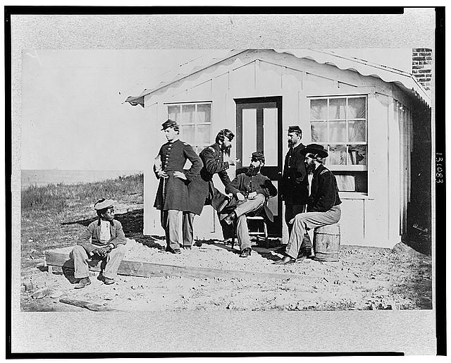 [Five Civil War soldiers gathered on dirt porch outside home. African American youth seated near them]