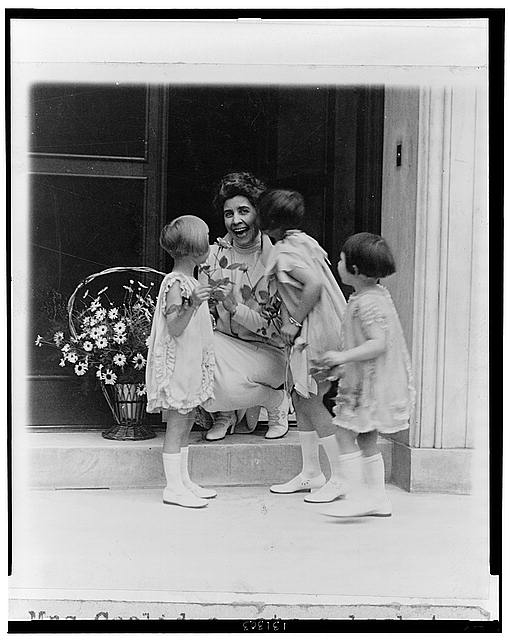 Mrs. Coolidge gets a basket of flowers and a kiss