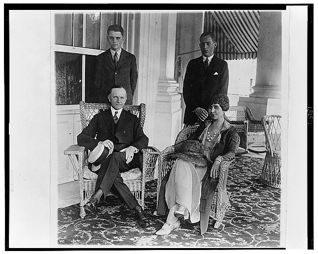 [President and Mrs. Coolidge, full-length portraits, seated on porch, with their two sons standing behind them]