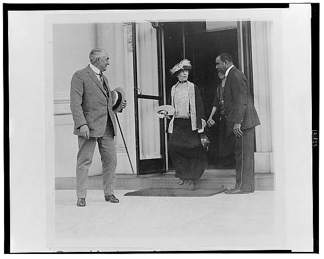 President Harding waiting patiently while Mrs. Harding bids good-by to the White House employees