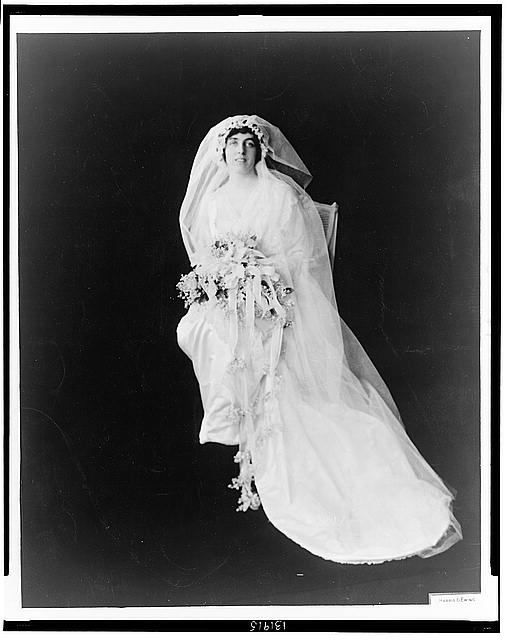 [Eleanor Randolph Wilson, full-length portrait, seated, facing front, wearing wedding gown and holding bouquet of flowers]