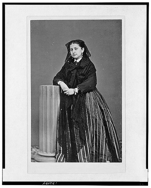 [Woman wearing shawl, full-length portrait, standing facing front, with arm propped on half column]