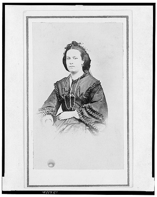 [Woman, half-length portrait, seated, facing front]