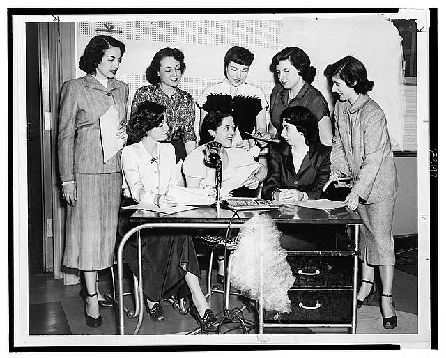 [Gathered behind desk and microphone celebrating radio station WNYC's 25th anniversary are (l to r) standing: Miriam Cutler, Dulcie Rogers, Marilyn Tack, Patti Bolton, Lynn Thiras and seated: Anita Paige, Lillian Blake, and Rita Ostrow]