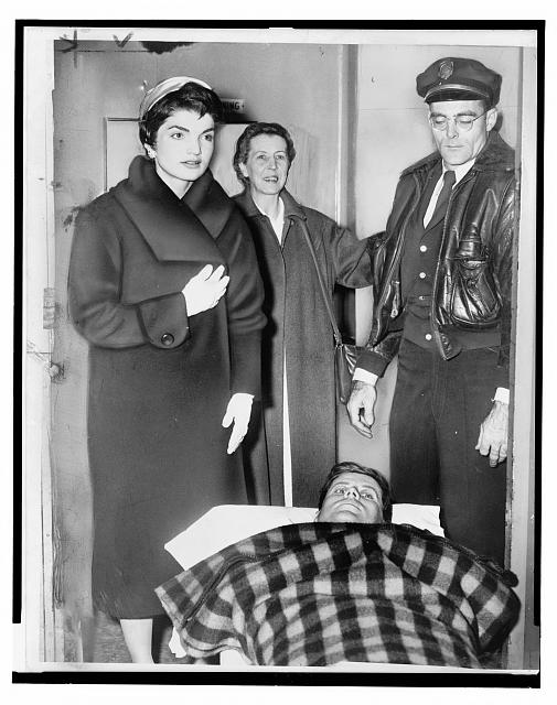 [John F. Kennedy leaving on gurney from hospital following spinal surgery, as his wife Jacqueline stands over him]