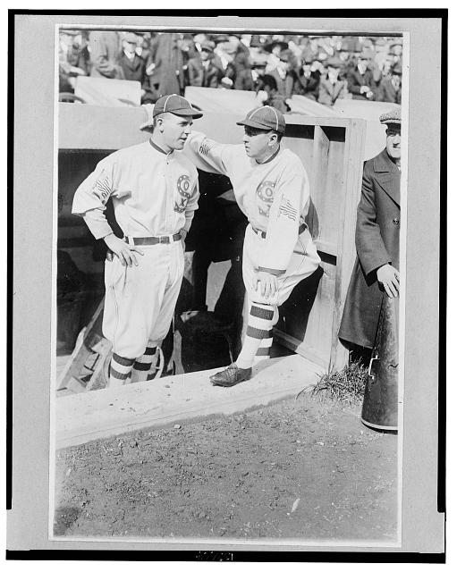 "[Clarence ""Pants"" Rowland, manager of the Chicago White Sox, (right) talks with his pitcher, Eddie Cicotte, (left) in the dugout during a game]"