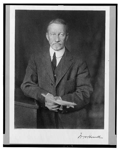[William H. Howell, half-length portrait, standing, facing front, leaning on lectern, holding papers]
