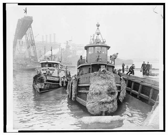 [U.S. Navy tugboat docks at the Brooklyn navy yard pier as a commercial tugboat departs to resume duties following a tugboat operators' strike]
