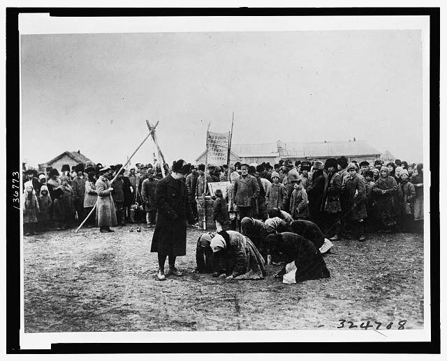 Hungry Russian women kneel before American Relief Administration officials