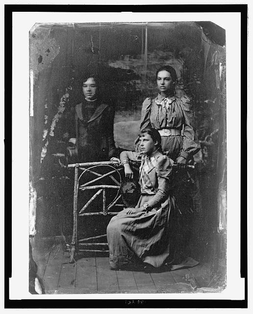"Marian ""Daisy"" Bell, left, and Elsie May Bell, right, standing, with an unidentified friend, seated"