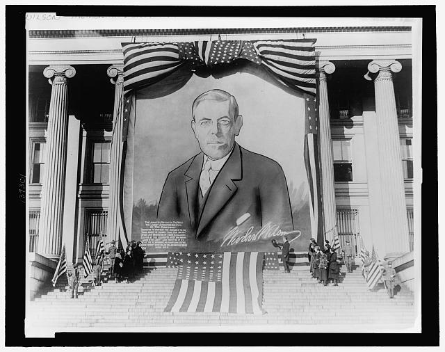 [Banner-size portrait painting of Woodrow Wilson hanging from a building]