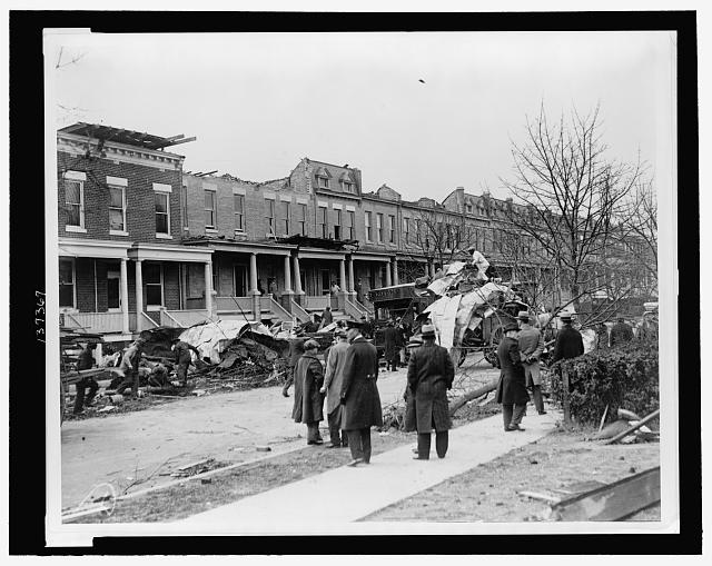 [Men watching debris being cleaned up at row houses on A St., NE, near 14th St., severely damaged by a tornado on Nov. 17, 1927]