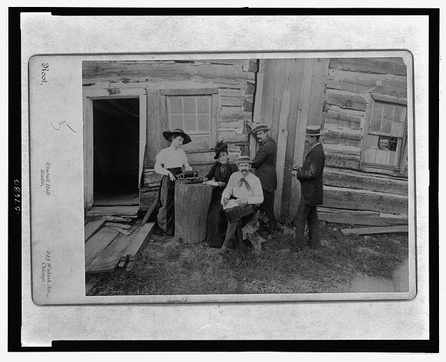 Front view of a portion of the Lincoln cabin with a group composed of Mrs. Norah Gridley, Miss Mary Coleman, the typewriter, the brothers Megar, architects, and Mr. Stille, and showing young Hall a great grandson of Tho Lincoln looking through the window of the east room of the cabin