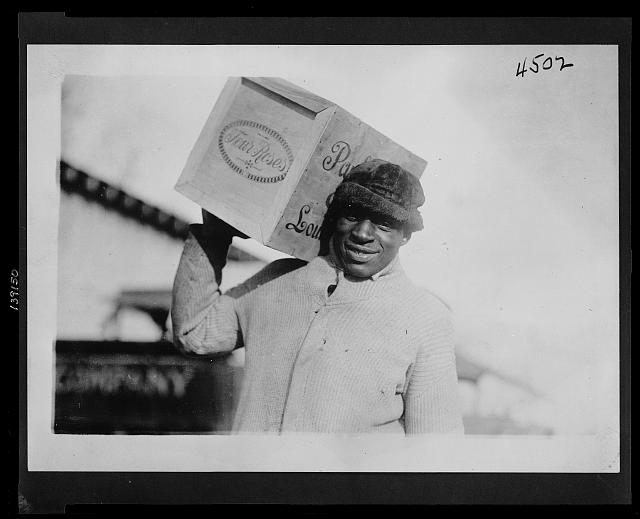 "[African American man carrying a case of ""Four Roses"" whiskey on his shoulder, possibly confiscated by the U.S. Internal Revenue Bureau]"