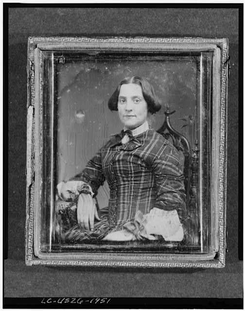 [Unidentified woman, half-length portrait, facing front, seated in chair with arm resting on table with tablecloth]