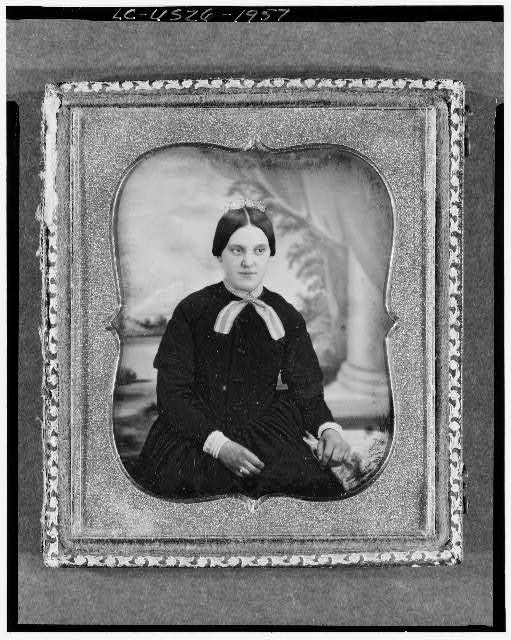 [Unidentified woman, three-quarter length portrait, facing front, seated before a painted backdrop with column]
