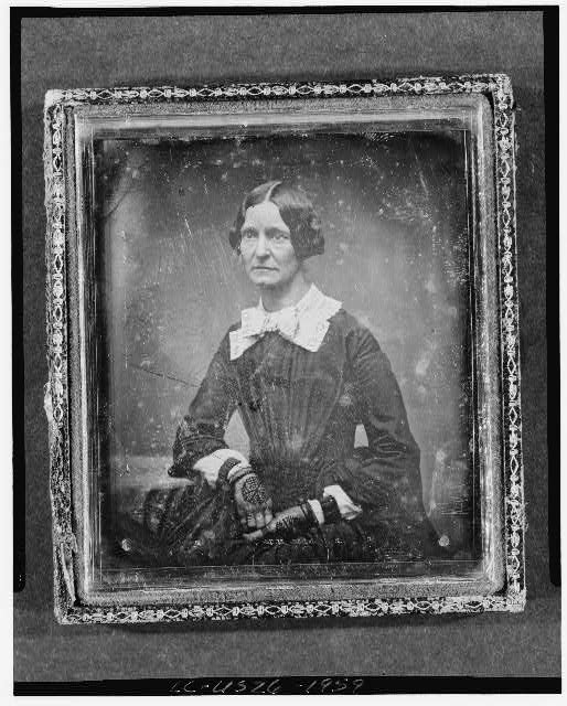 [Unidentified woman, three-quarter length portrait, three-quarters to left, seated next to table with tablecloth]