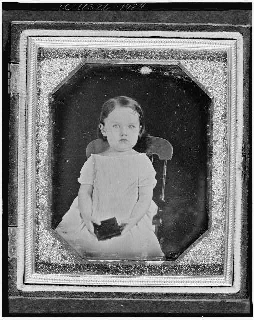 [Unidentified girl, three-quarter length portrait, facing front, seated in chair, holding a daguerreotype case(?)]