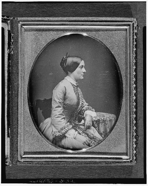 "[Ann Minerva ""Nannie"" Rodgers Macomb, three-quarter length portrait of woman, facing right in profile, seated in chair with arm resting on table with tablecloth]"
