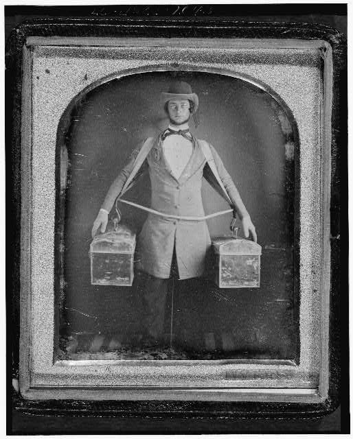 [Occupational portrait of a peddler, full-length, standing, facing front, with two bags held at his sides by a harness, neck brace visible between legs]