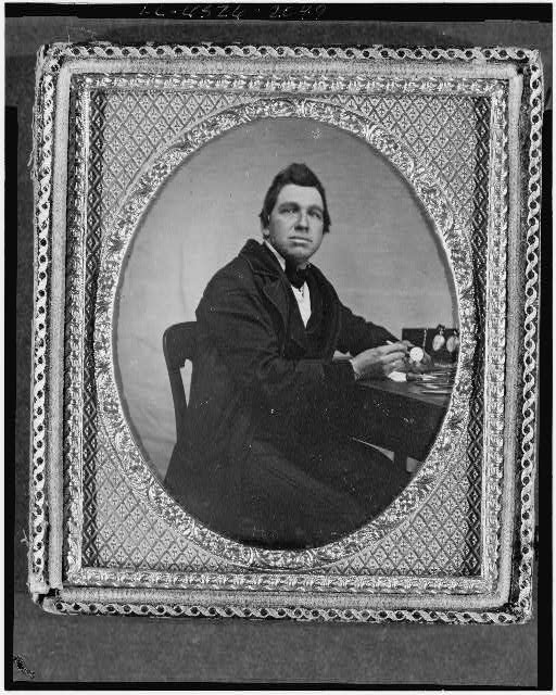 [Occupational portrait of a watchmaker, three-quarter length, seated at table with watches]