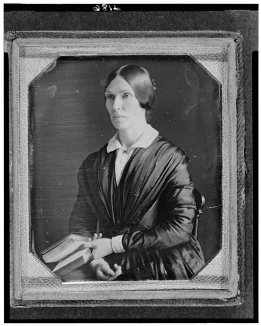 [Unidentified woman, half-length portrait, facing left, seated holding book]