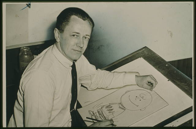 [Charles Schulz, half-length portrait, facing front, seated at drawing table with drawing of Charlie Brown]