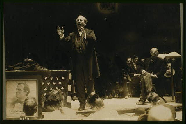 [William Jennings Bryan, full-length view standing on stage, delivering campaign speech, another man seated to the rear of the stage]